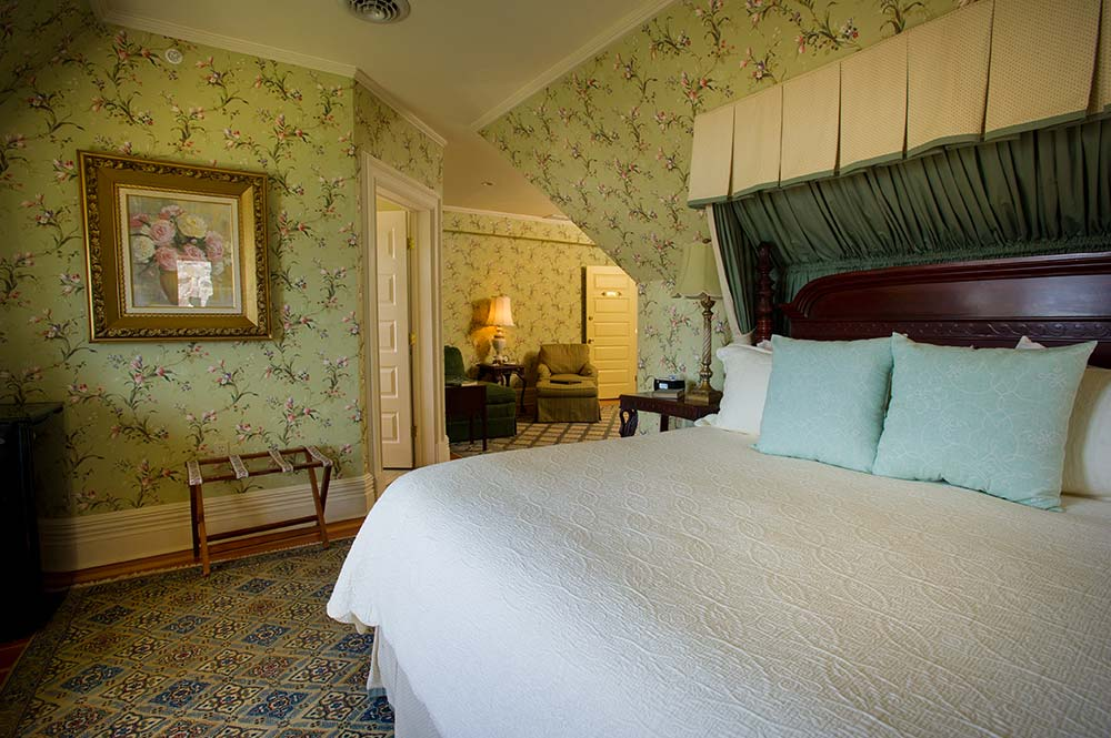 Green wallpapered room with bed and with adjacent sitting area