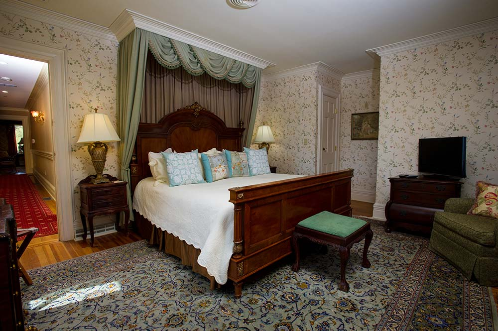 large bed in Bedroom with wood headboard and footboard