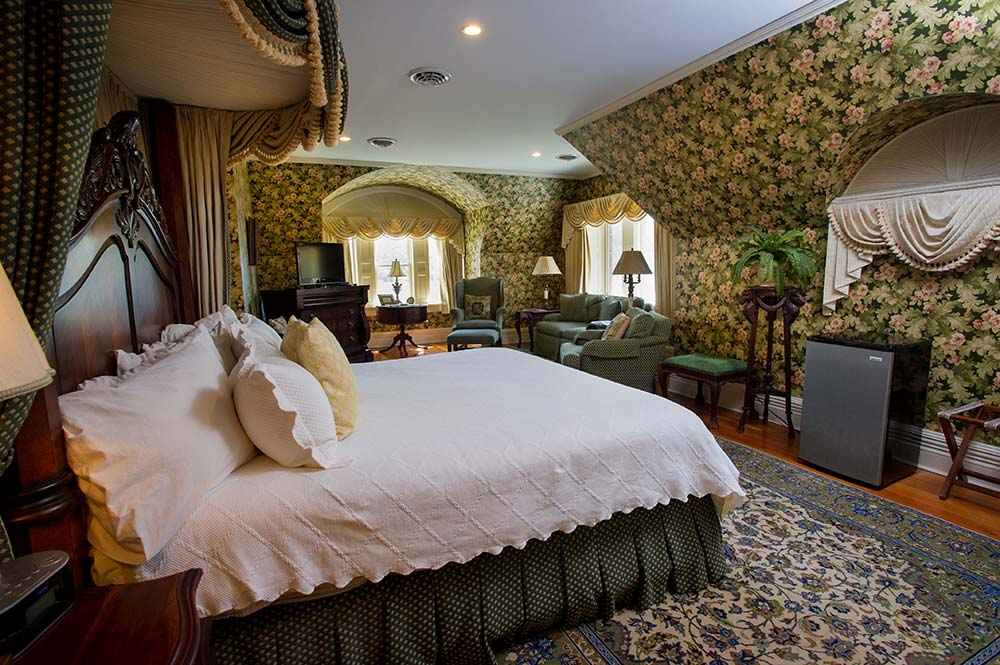 Floral wallpapered room with large bed and sitting area