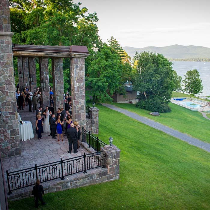 Wedding gathered on stone patio overlooking lake