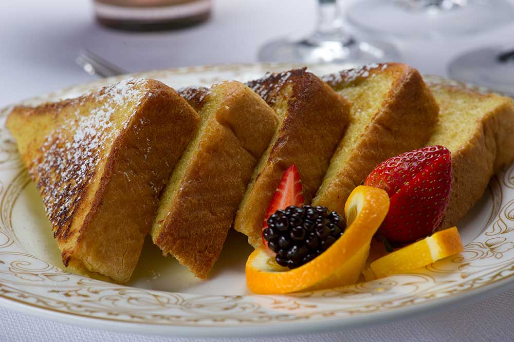 French toast on plate with powered sugar with fruit on side