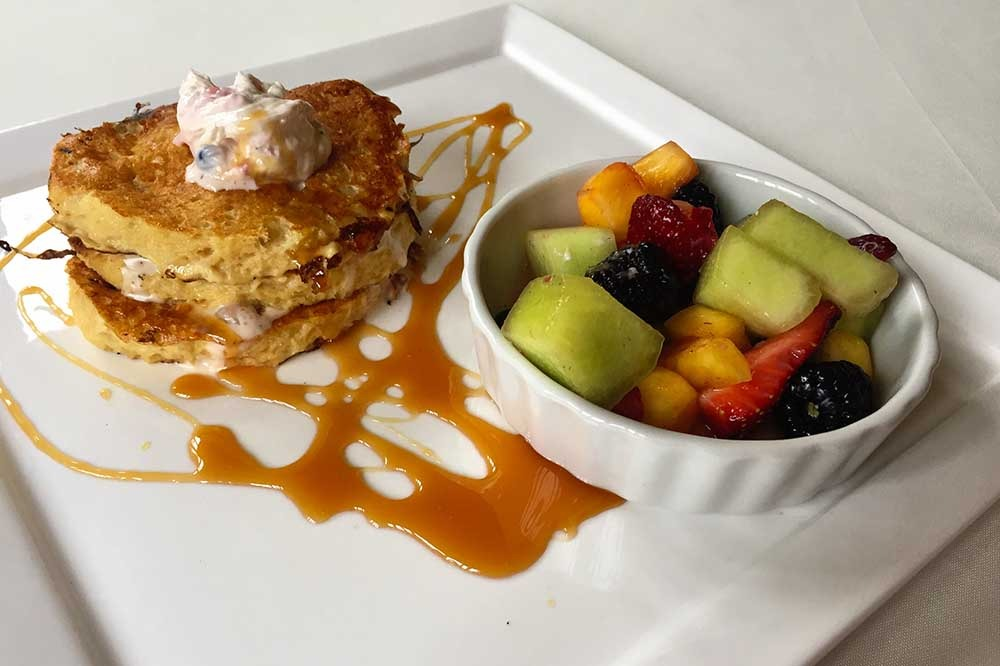fluffy pancakes with caramel sauce and side of fruit