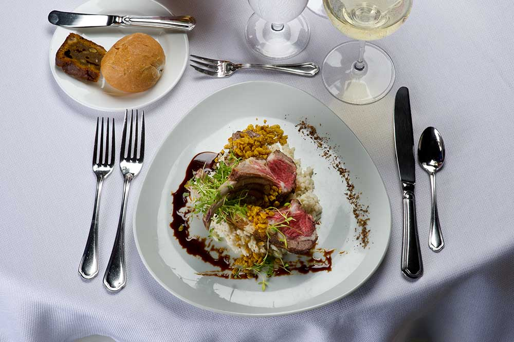 elegant dinner on plate with silverware and rolls