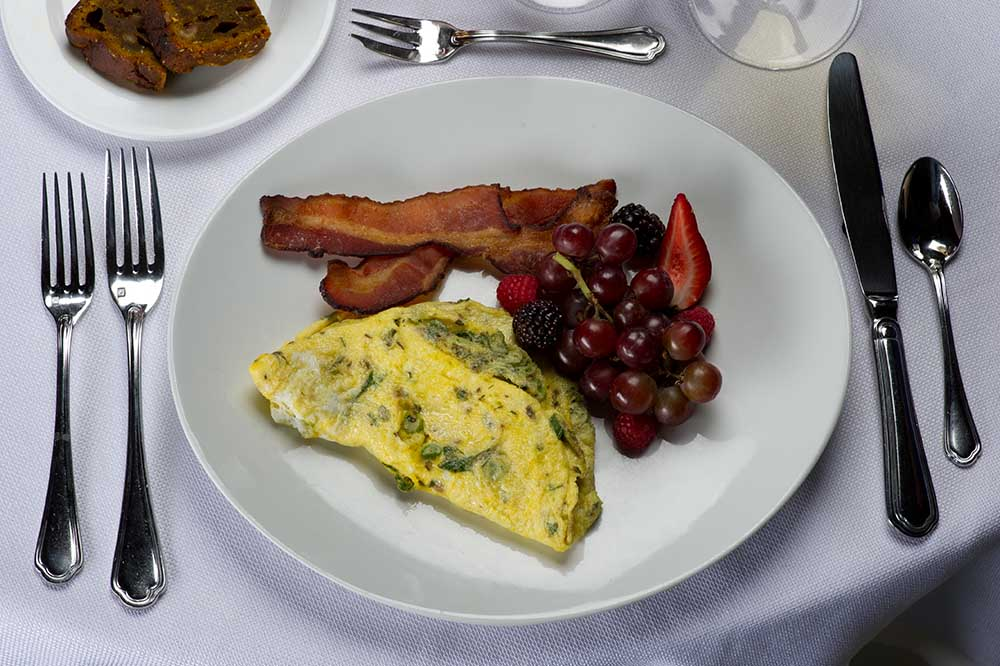 breakfast - grapes, omelet and bacon on plate
