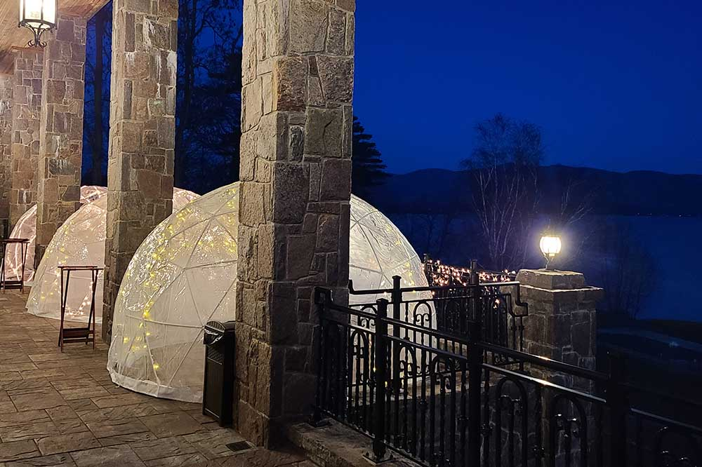 tables setup in clear domes for eating outside during winter