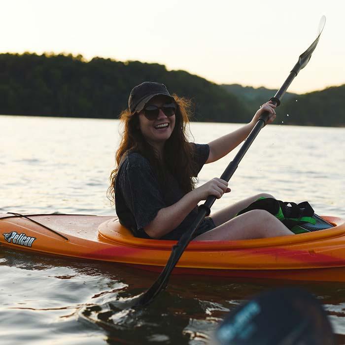 Women in orange kayak on lake