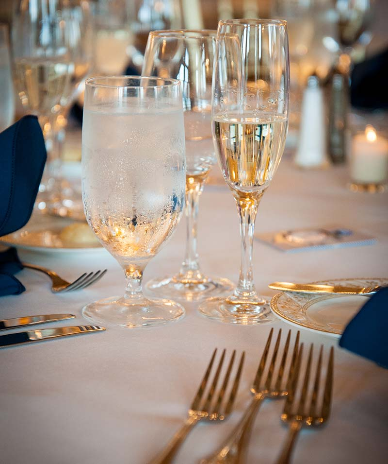 Champagne glass and gold silverware on wedding dining table