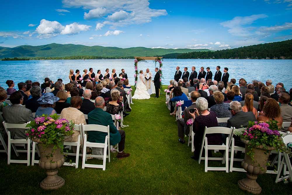 wedding ceremony on grass next to lake