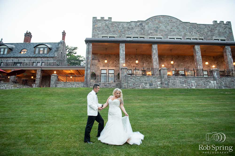 Bridge and Groom pose for photo on lawn