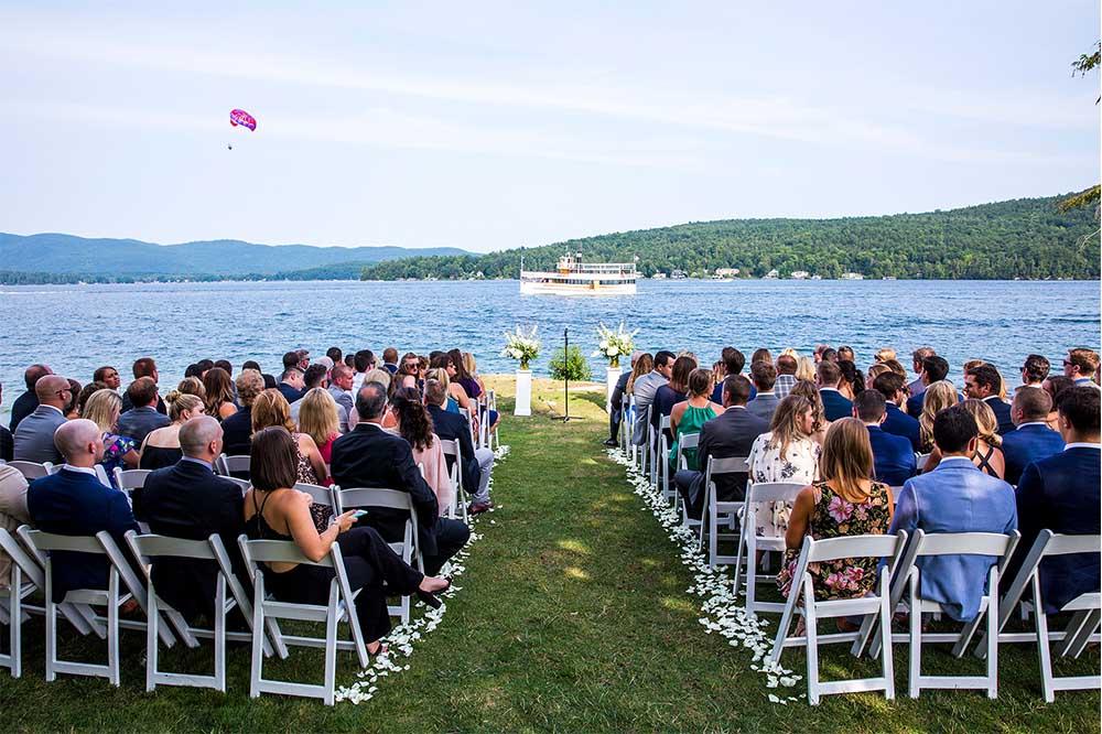 wedding ceremony next to lake with cruise ship