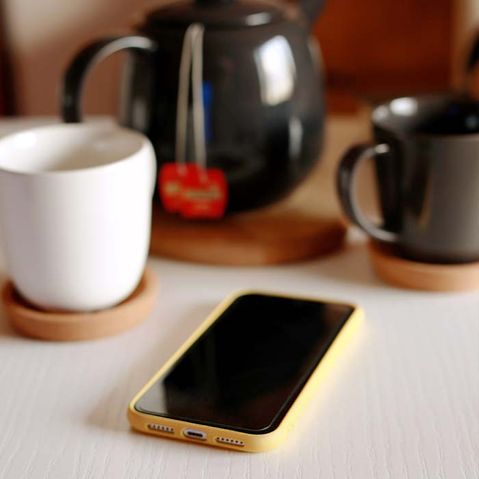 phone next to coffee cups and pot