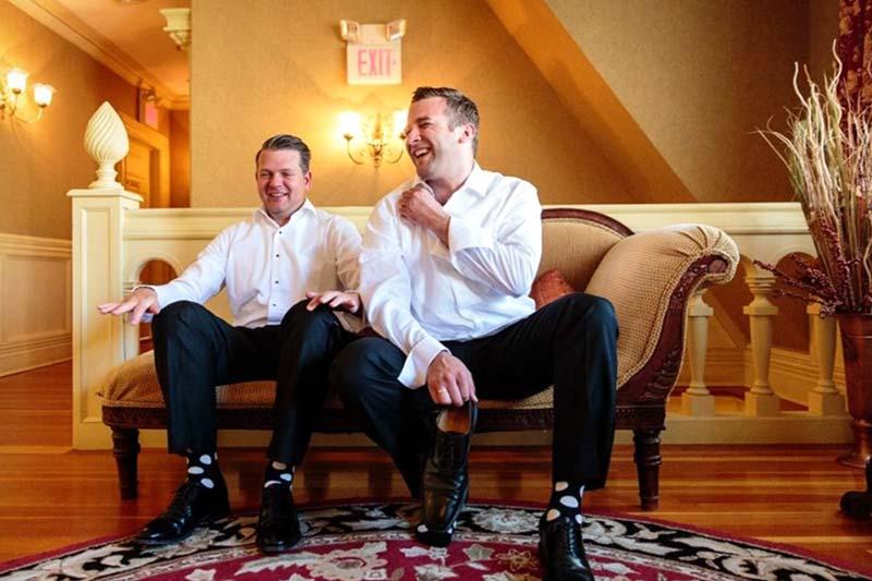 2 men preparing for wedding sitting on bench