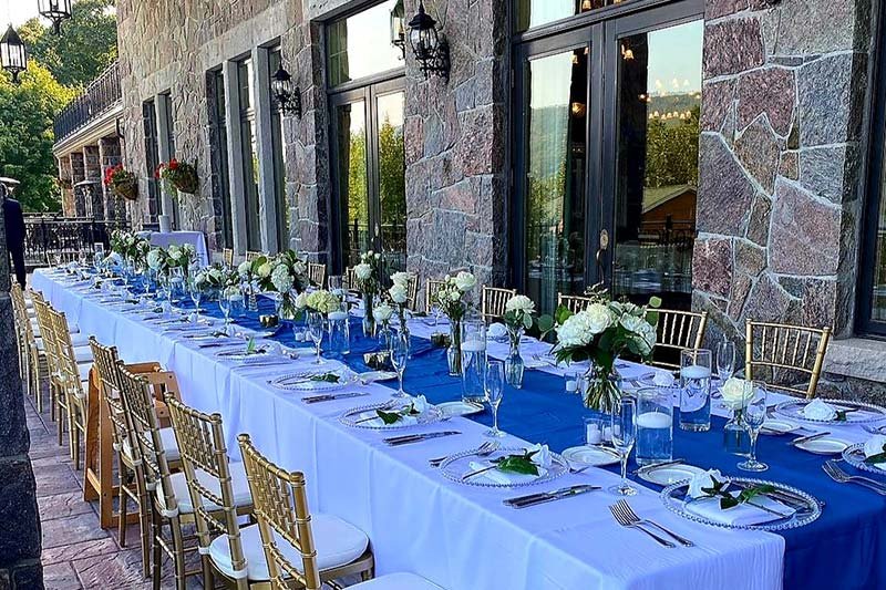 Long table at wedding reception with blue tablecloth