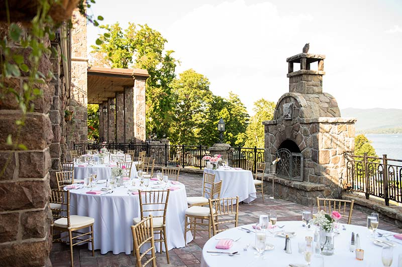 Dining tables setup on terrace with large stone fireplace