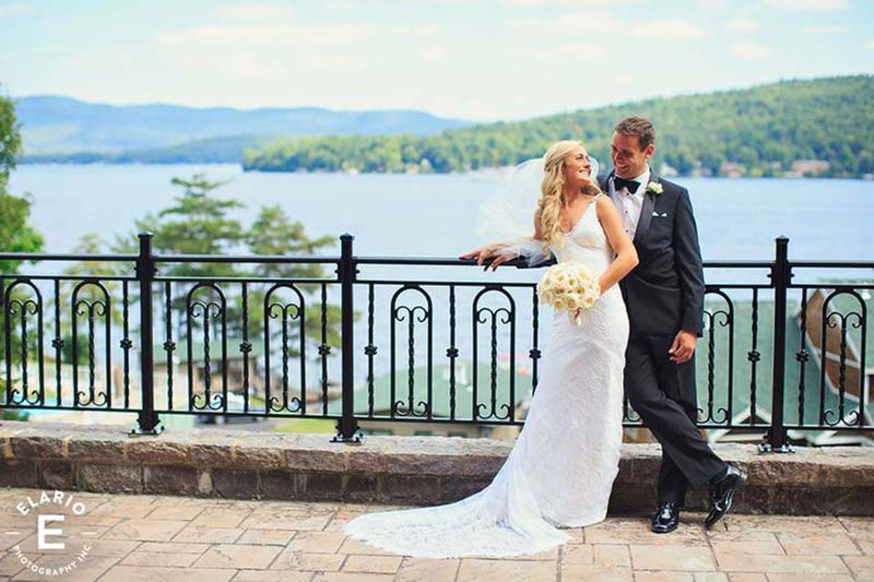 Bride and Groom posing for photo on Terrance overlooking lake george