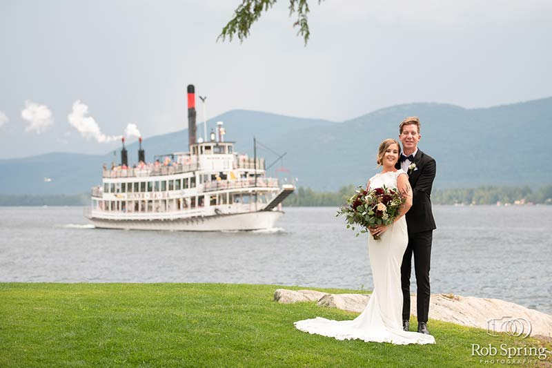 Bride and Groom on shore of lake george with Paddle boat in background